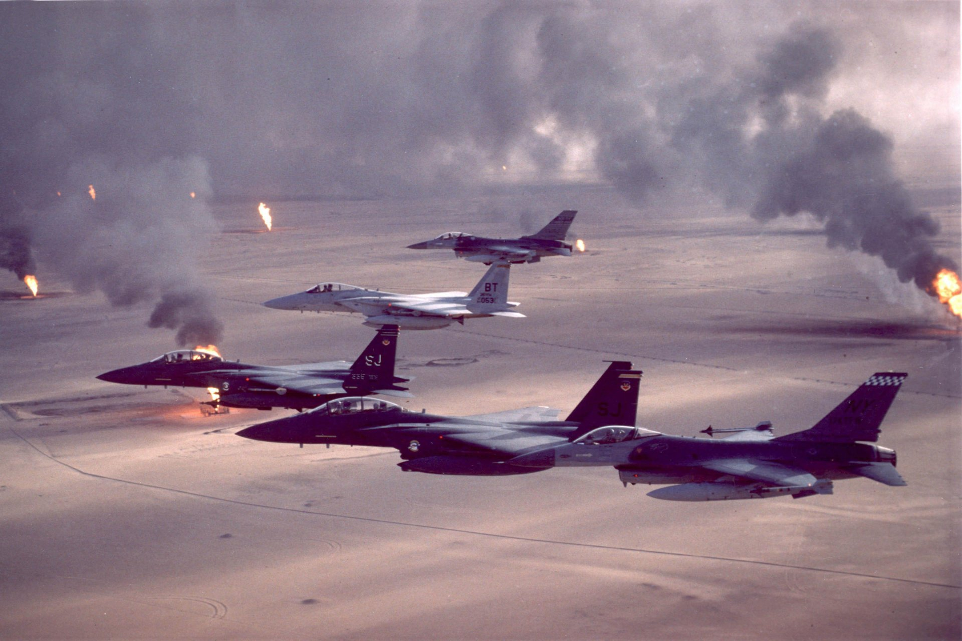 F-16A Fighting Falcon, F-15C Eagle and F-15E Strike Eagle fighter aircraft fly over burning oil field sites in Kuwait during Operation Desert Storm. (U.S. Air Force archive photo.)