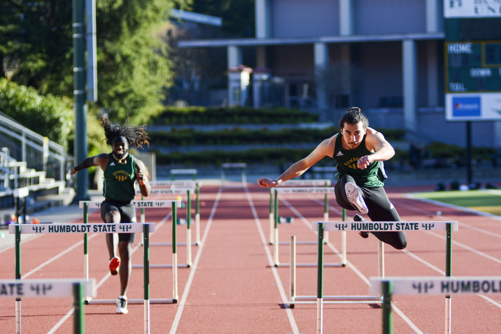 Humboldt State junior Henry Hagen (right) leads his teammate Travis Allen in the 60 meter hurdles rave at an inter-squad meet at the Redwood Bowl on Friday, March 12 | Photo by Elliott Portillo