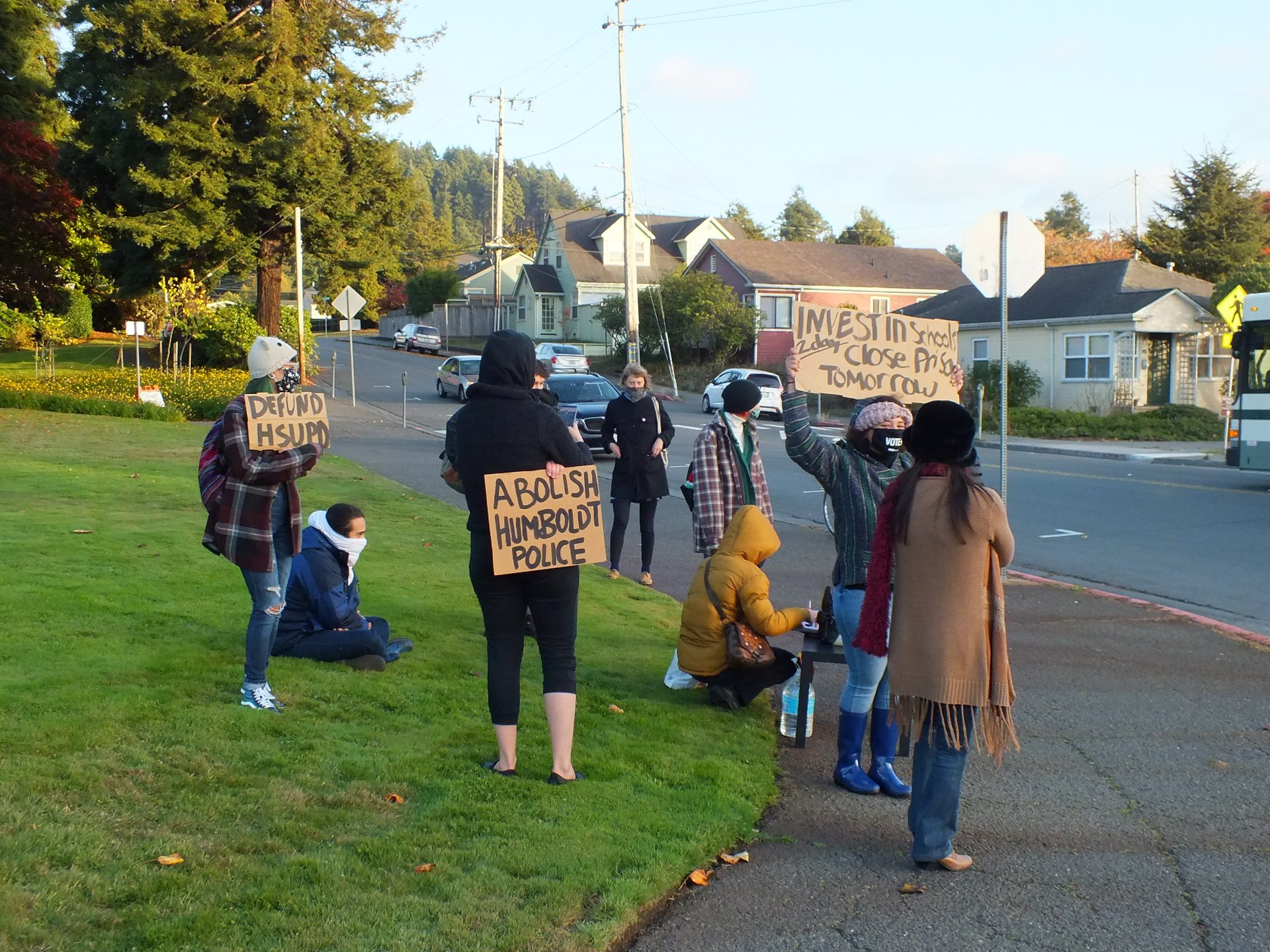 A small group gathered outside Humboldt State University on Nov. 7 to protest the campus police department. Part of a two day event, the crowd held signs and chanted at passing cars, who honked in support. | Photo by Carlos Holguin