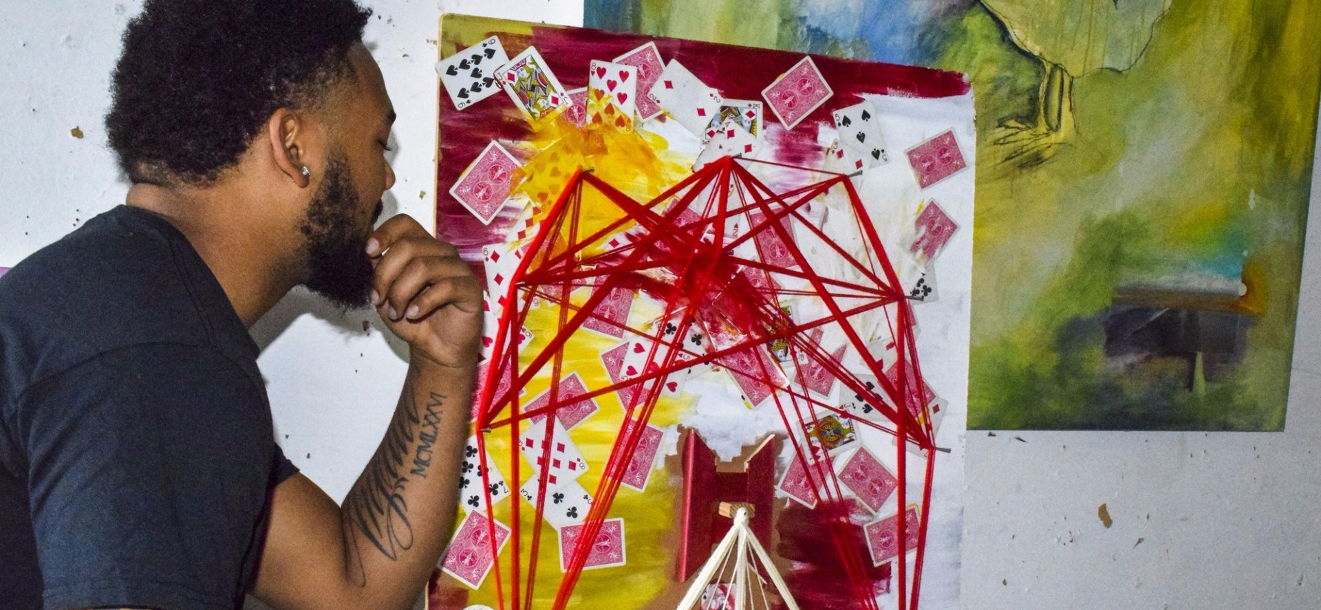 Adonnis Johnson looking deep into his abstract creation of cards and strins. Photo credit: Juan Herrera