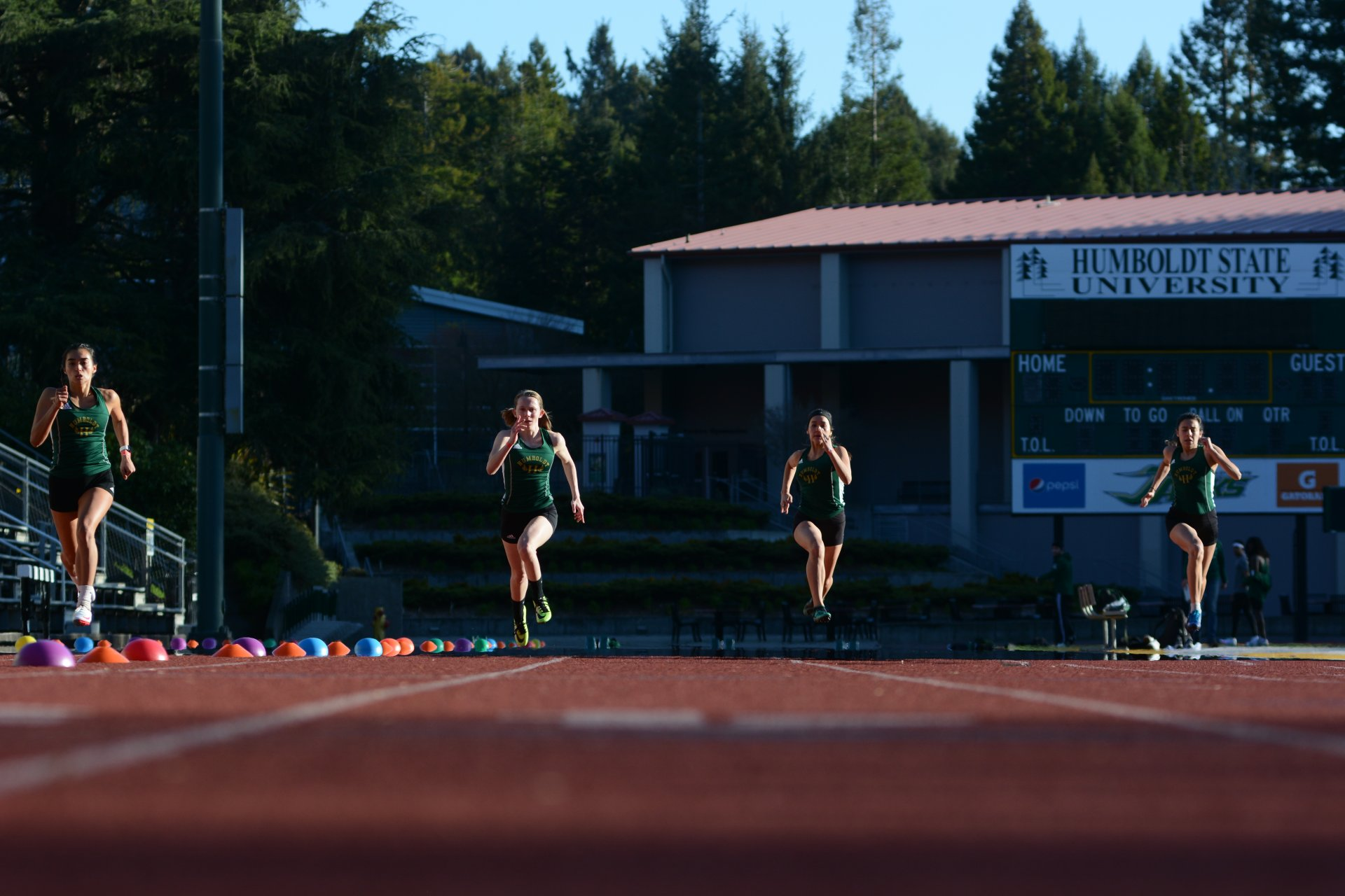 From left to right: Joy Hano, Christina Roberds, Lilyahna Engbretsen and Violeta Gutierrez race the 100 meter dash at an inter-squad meet at the Redwood Bowl on Thursday, March 11. | Photo by Elliot Portillo