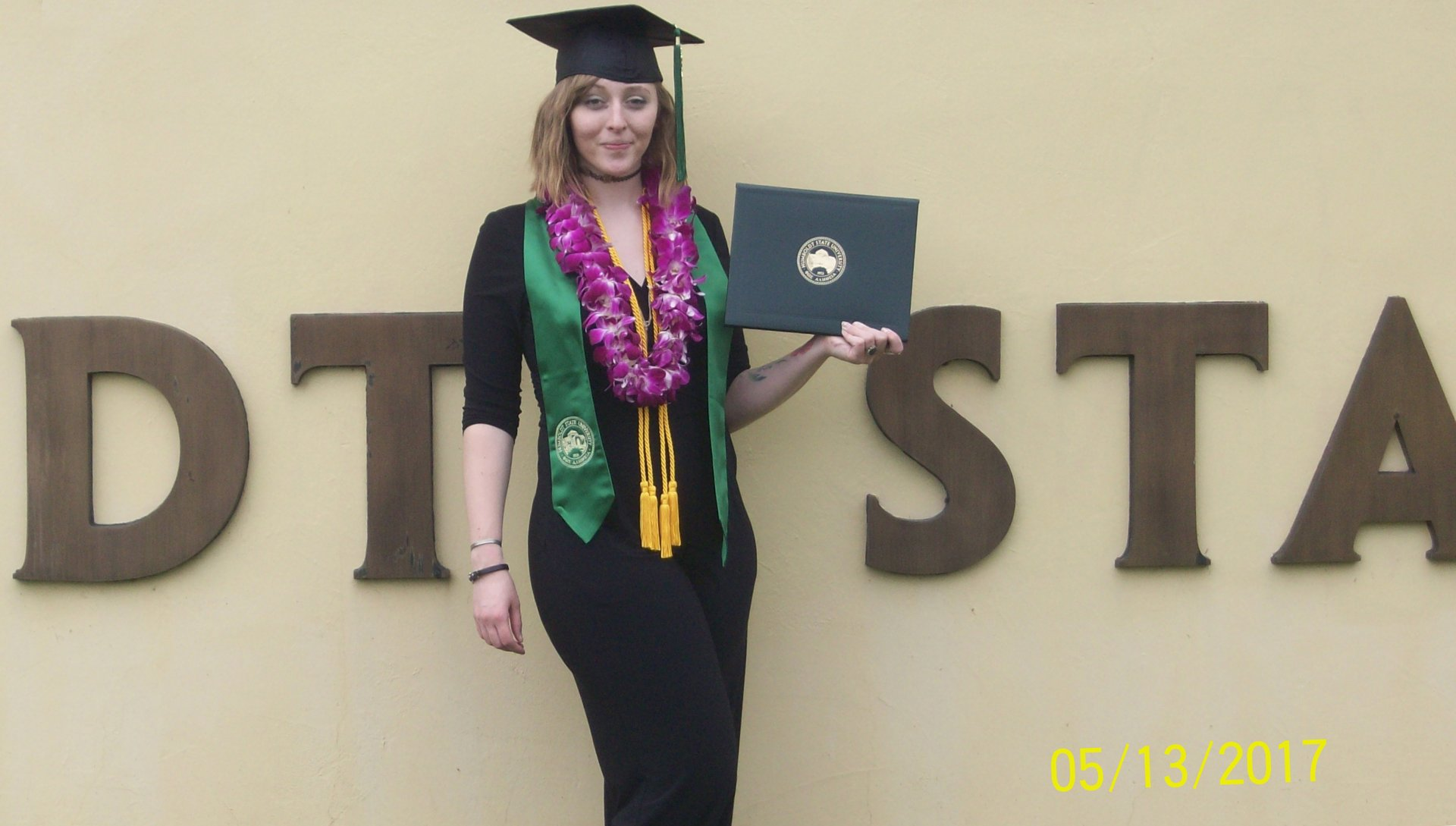 Erin Henry posing with her degree at Humboldt State University. Photo submitted by Tom Henry, father of Erin.