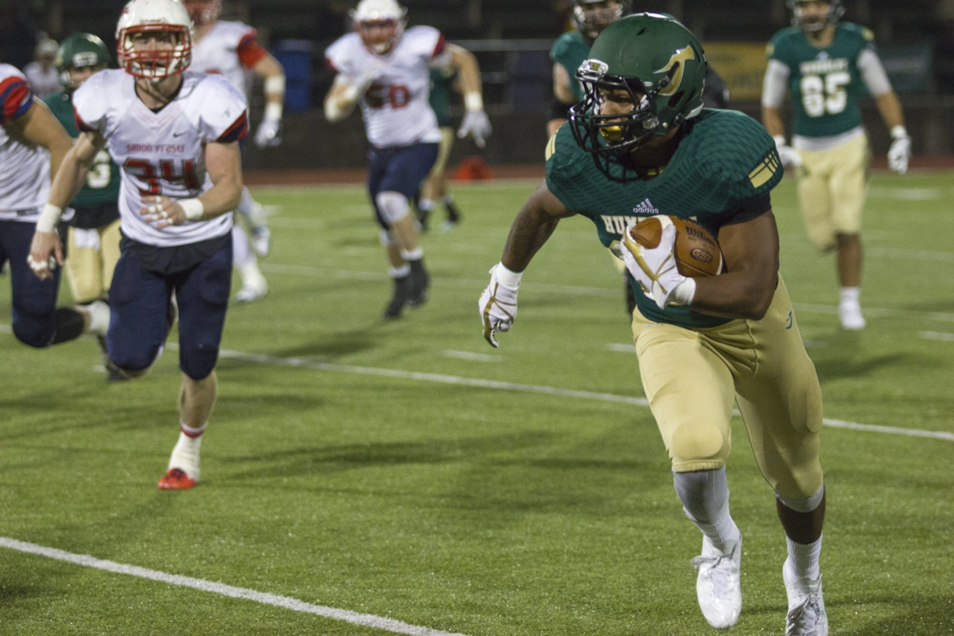 Isaiah Hall, right, gets to the edge of the field and turns toward the end zone for the Humboldt State University offense while defeating Simon Fraser 72-14 on Saturday, Sept. 16. | Photo by Diego Linares