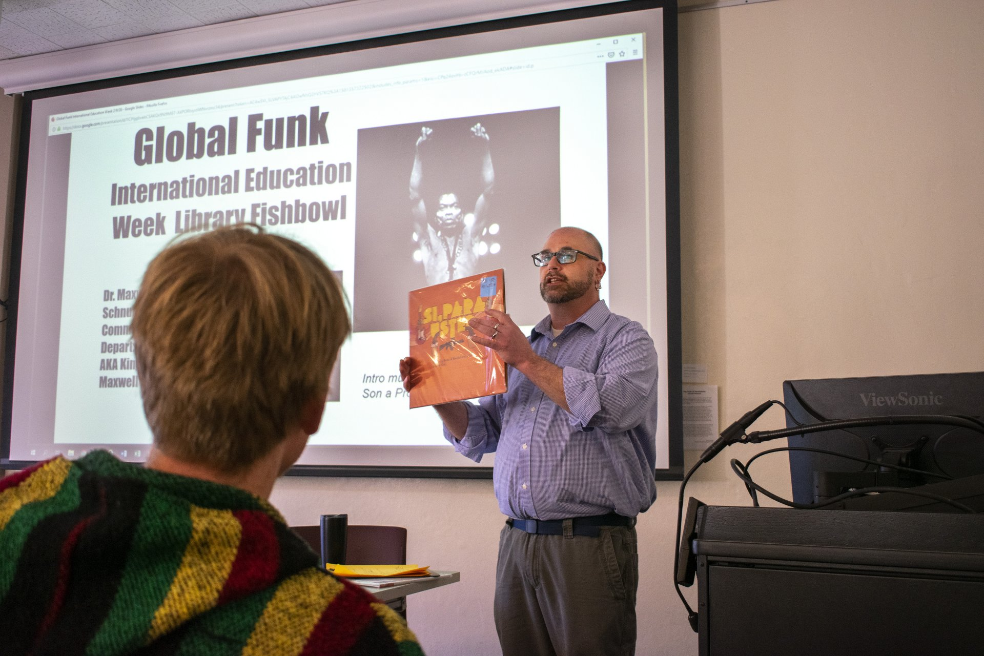 Local DJ and HSU Communication Department Chair Maxwell Schnurer shows off a funk album in his hour-long talk on global funk music on Feb. 10 at the HSU Library Fishbowl. Schnurer described funk as a combination of revolutionary practice and a desire to get down. | Photo by James Wilde