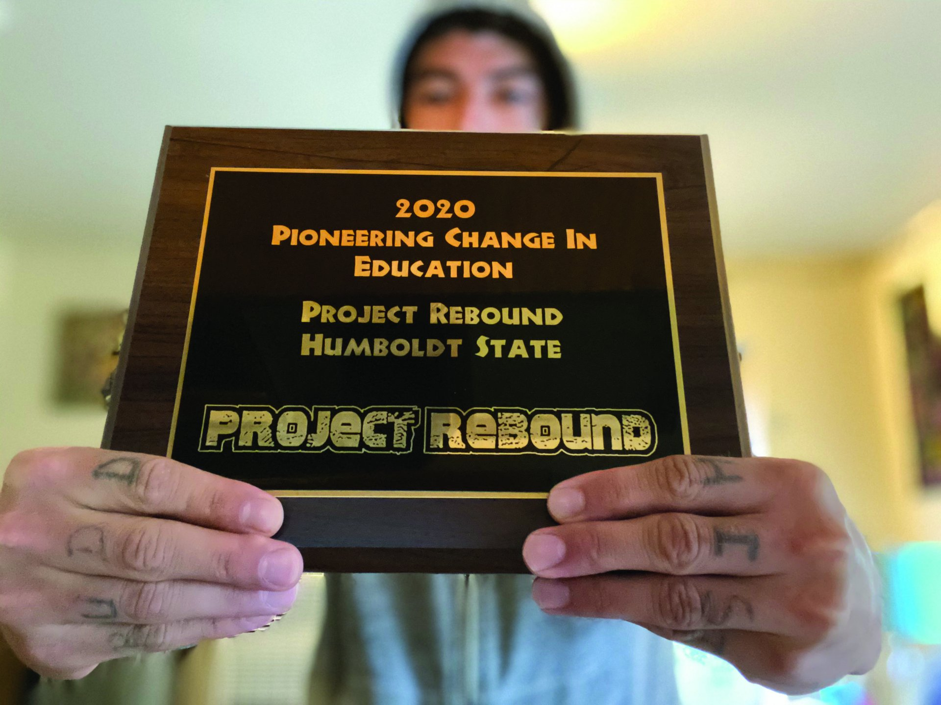 Tony Wallin holds the  plaque recognizing the Humboldt State chapter of  Project Rebound.  For Wallin, the creation of this group was personal for Wallin as a formerly incarcerated  student. | Photo by Carlos Holguin
