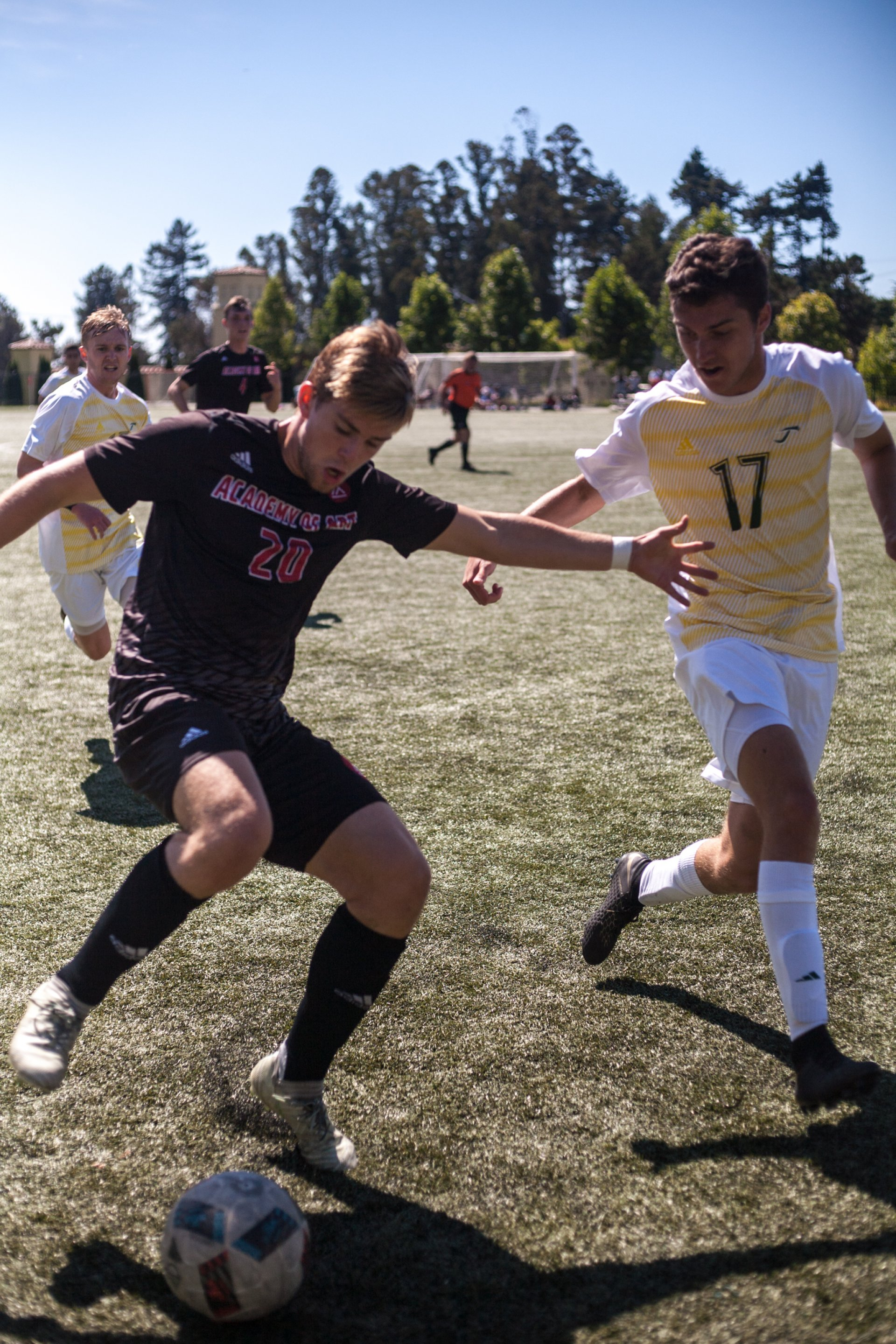 Lumberjacks sophomore midfielder Ethan Waters (20) moves in to steal the ball from Academy of Art's freshman forward Edvard Edvarsson on Sept. 9 at College Creek Field. | Photo by Emily Osthimer