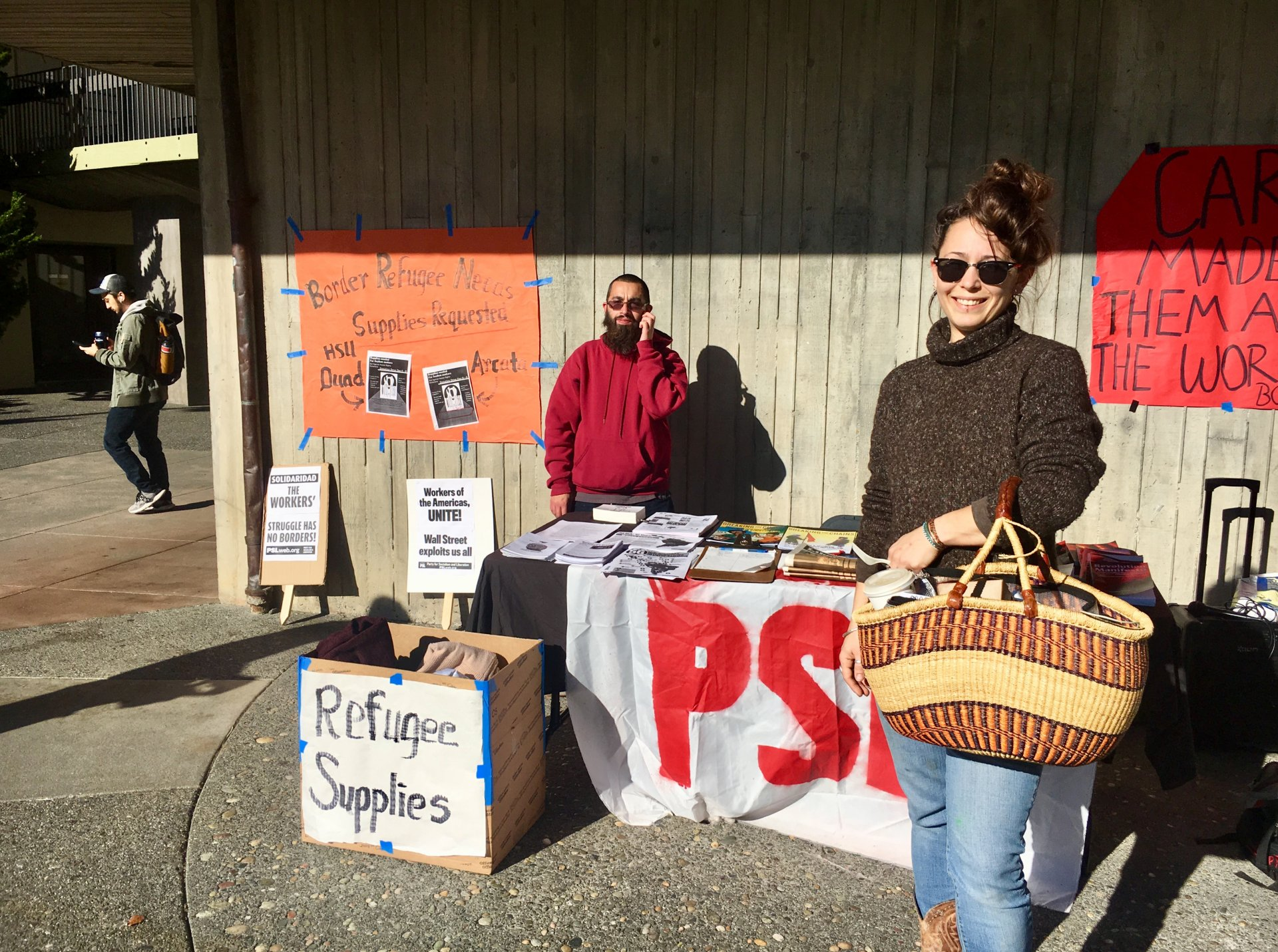 Annie Bond stands in front of the PSL table at the migrant caravan donation drive on Dec. 6. Photo by Freddy Brewster
