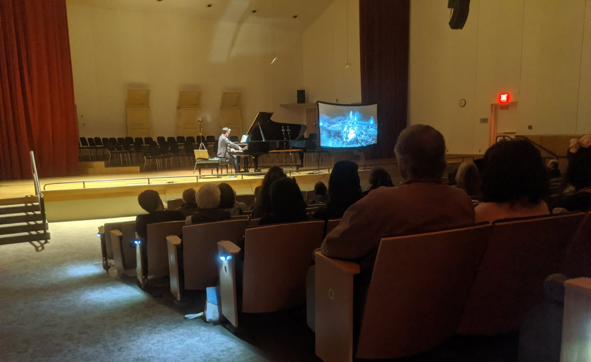 Ryan McGaughey playing songs from Final Fantasy VII arranged for piano by Shiro Hamaguchi in Fulkerson Recital Hall Feb. 21. The projector beside McGaughey cycled through footage form the Final Fantasy games and movie. | Photo by Walker B. True
