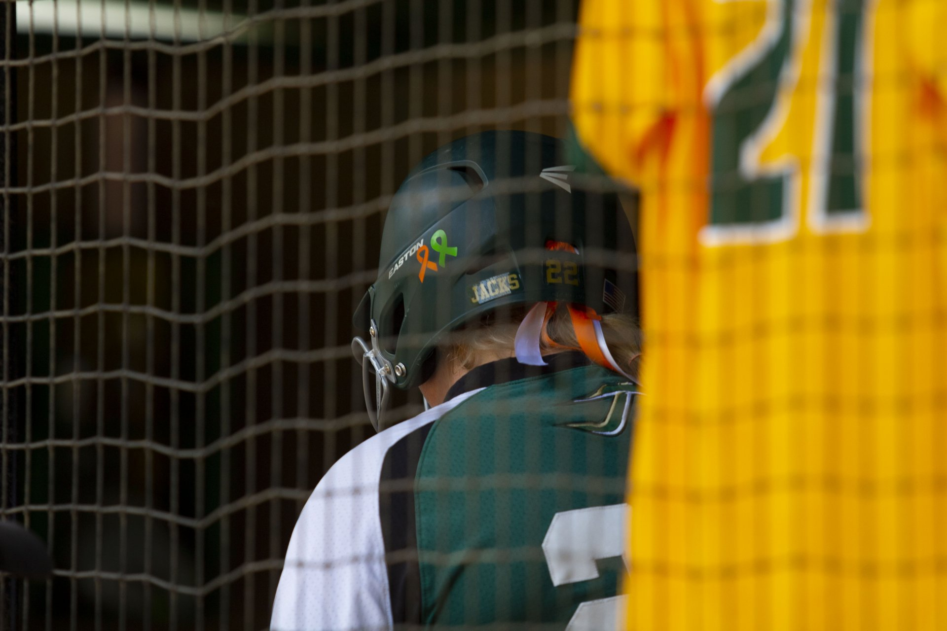 Sophomore Humboldt State softball player Anna Brondos walks through the dugout past Evelyn Andrew's number 21 jersey with ribbons on her helmet to remember her during the Lumberjacks game against Chico State on Feb. 22 at HSU Softball Field. | Photo by Thomas Lal