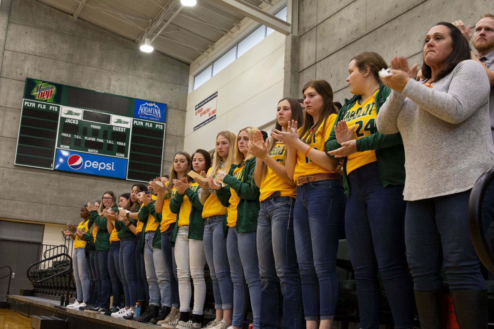 Members of the Humboldt State softball team stand and applaud with Head Coach Shelli Sarchett as they honor teammate Evelyn Andrews at her celebration of life event at Lumberjack Arena on Feb. 23. | Photo by Thomas Lal