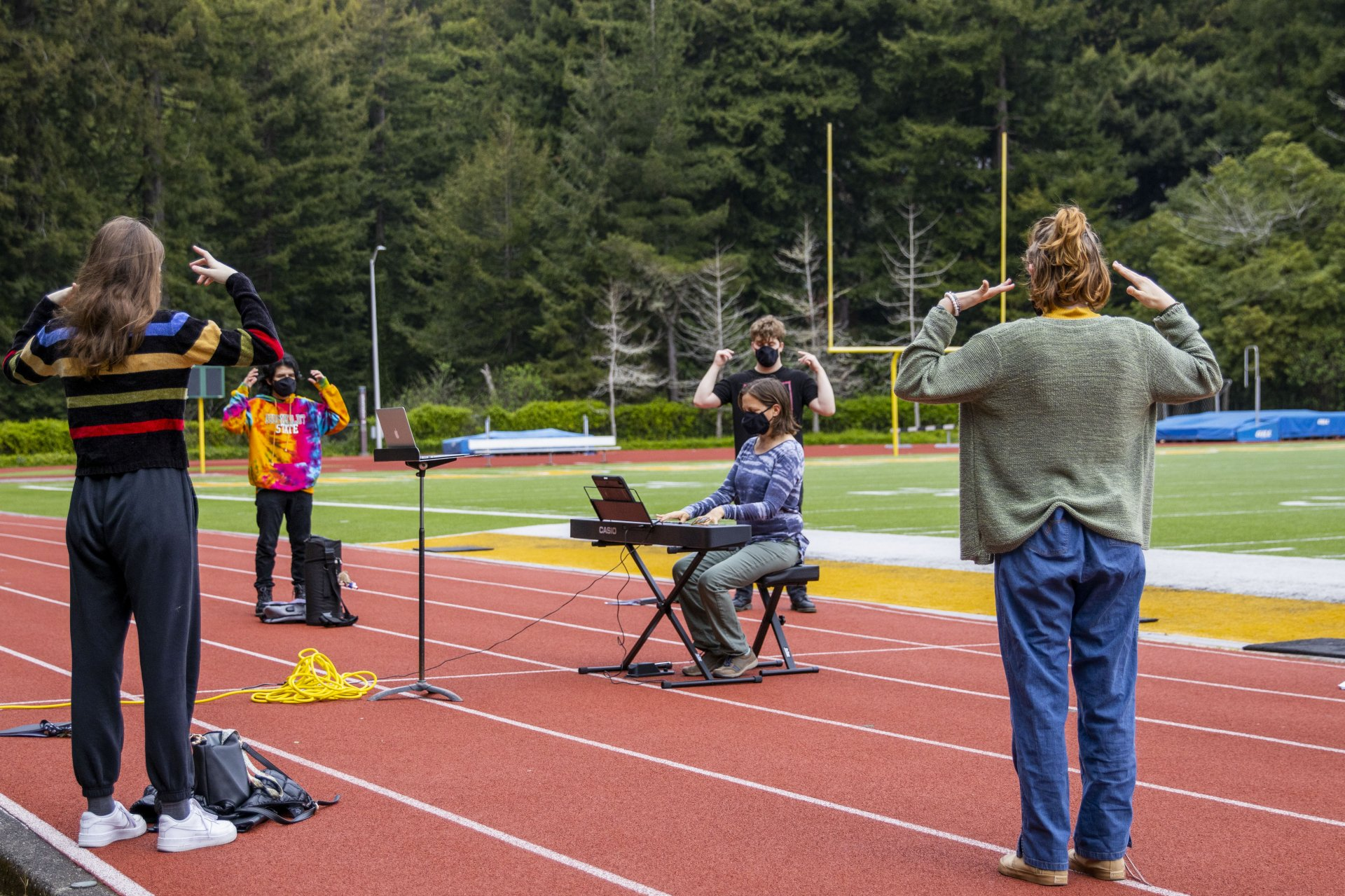 Humboldt State Professor Rachel Samet plays the piano as she walks her MUS 106B University Singers class through voacl warm-ups in the morning outside in the Redwood Bowl arena on the HSU campus on April 5. | Photo by Thomas Lal