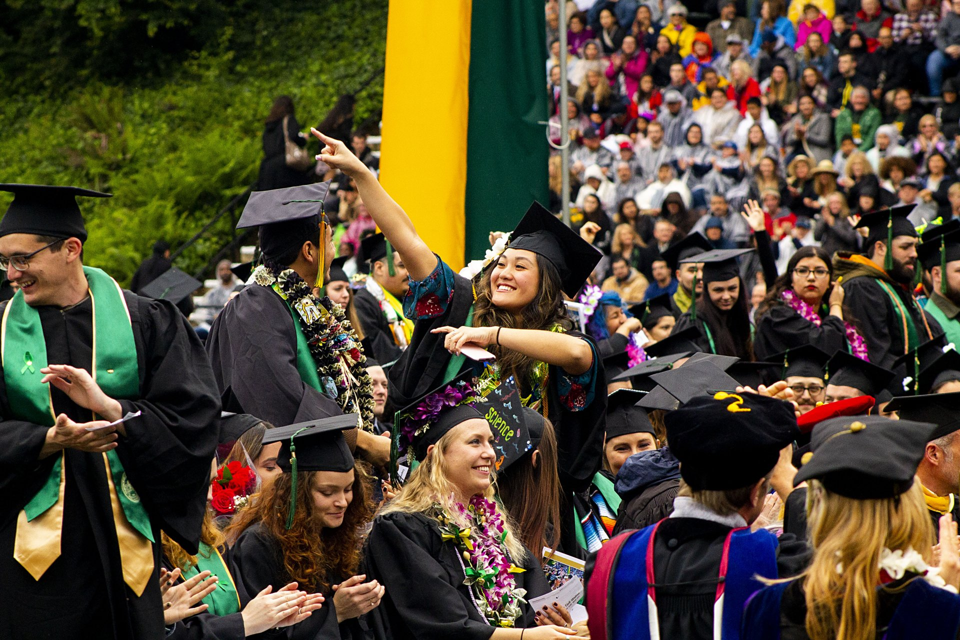 A student points off to someone in the crowd at the 2019 graduation ceremony while graduates from the College of Natural Resources and Sciences settle in on May 18,2019 at the Redwood Bowl. | Photo by Thomas Lal
