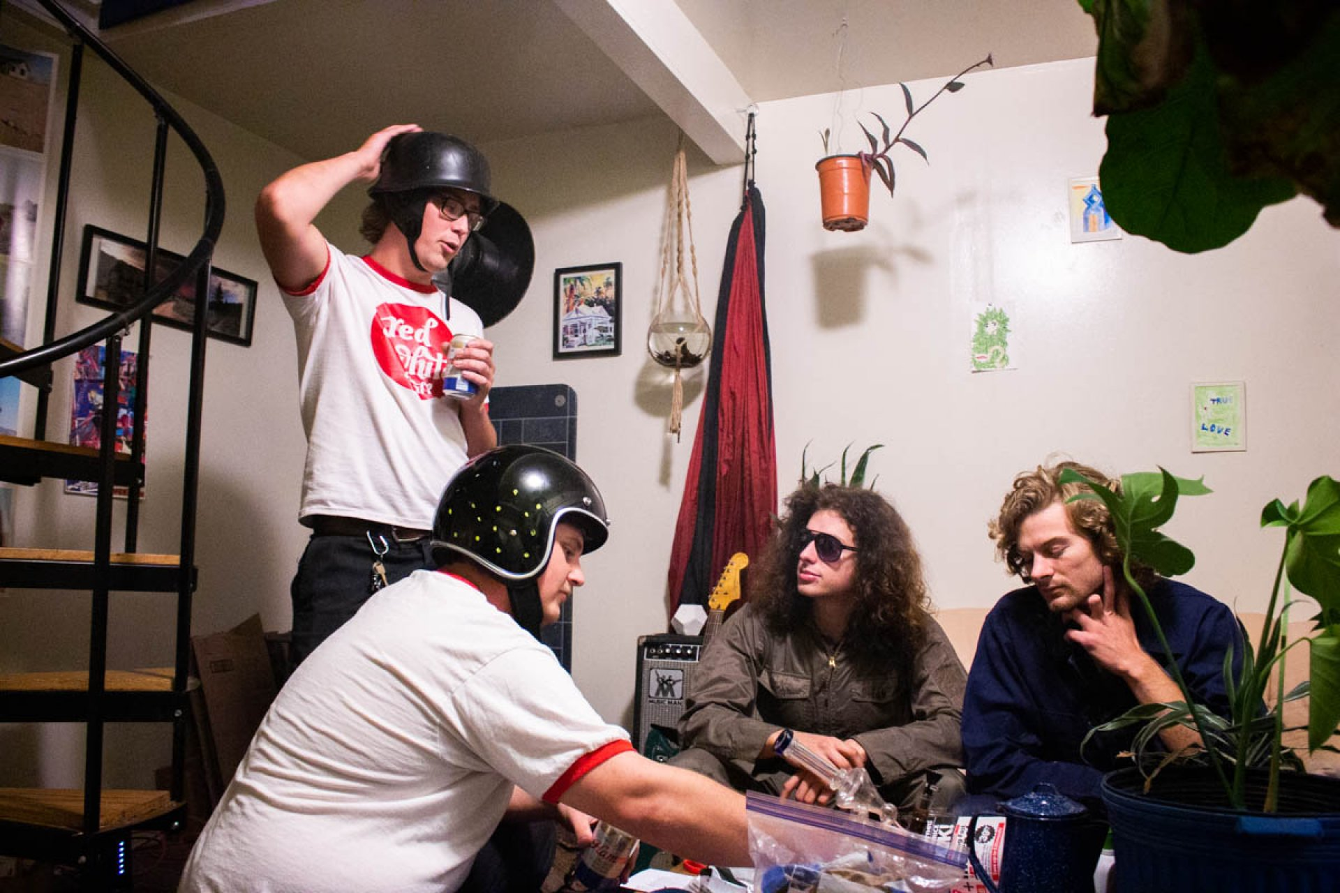 Band members Wyatt Brenner, Willem Kernkamp, Delphin Browne and Quonton Waull sit around a table and play games. | Photo by Jerame Saunders
