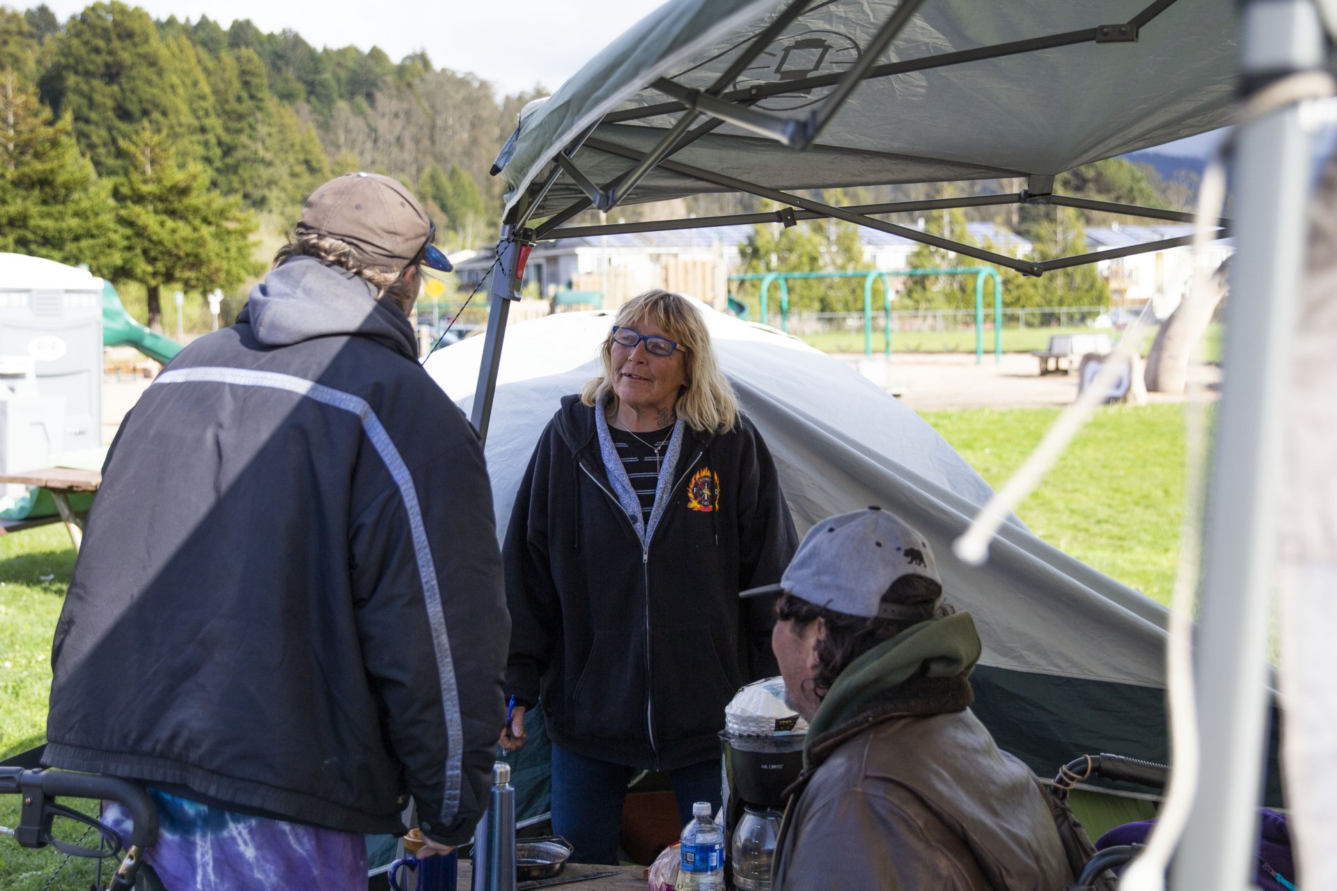 Jim Kelly, Crystal Fisher and David Love talk with each other at their makeshift camp outside the Arcata Community Center during the COVID-19 pandemic on March 6. | Photo by Thomas Lal