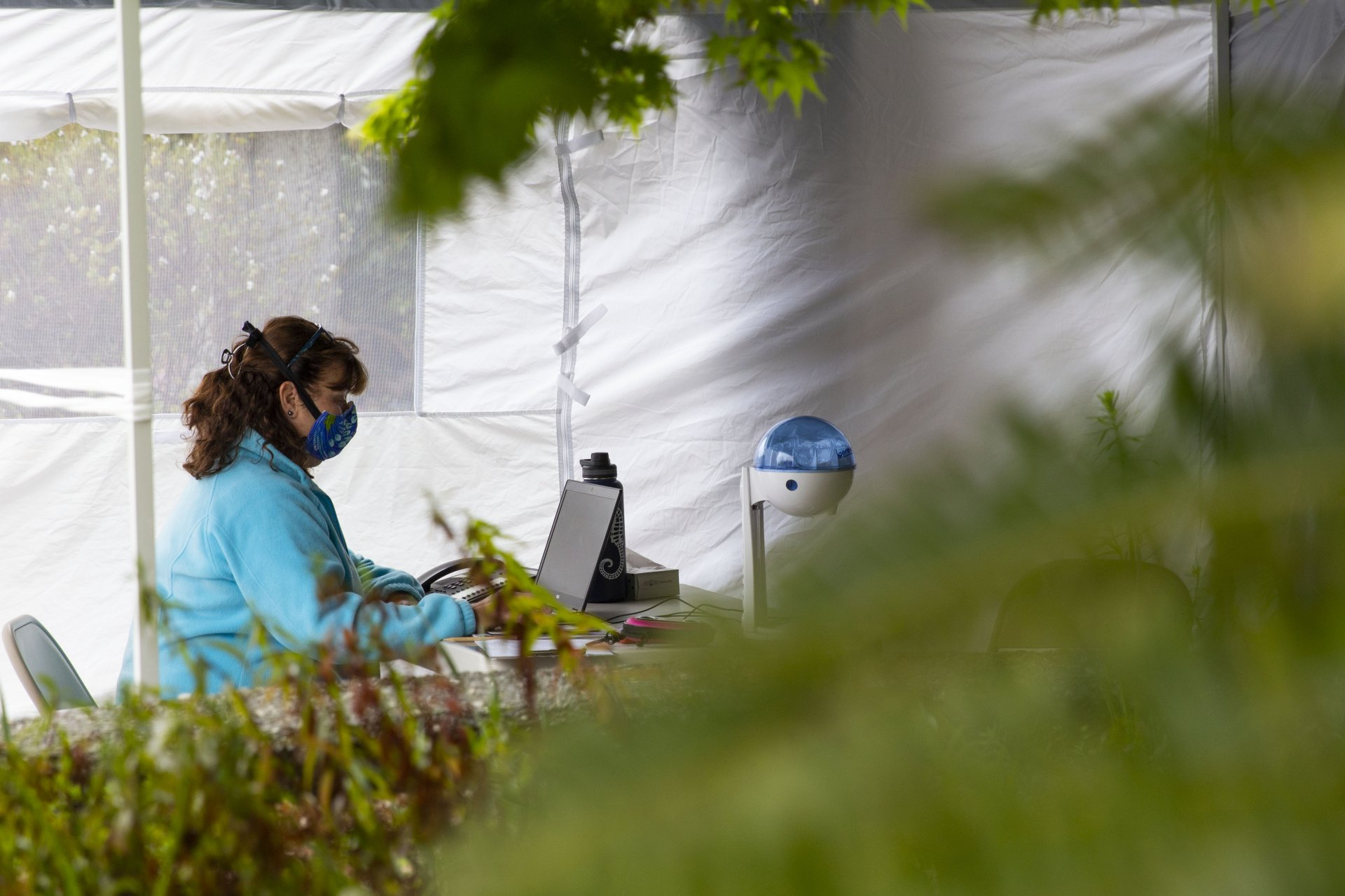 Chris Mis, a registered nurse who works part time at the Student Health Center works at her computer under a tent outside during the Covid-19 pandemic on April 17. | Photo by Thomas Lal