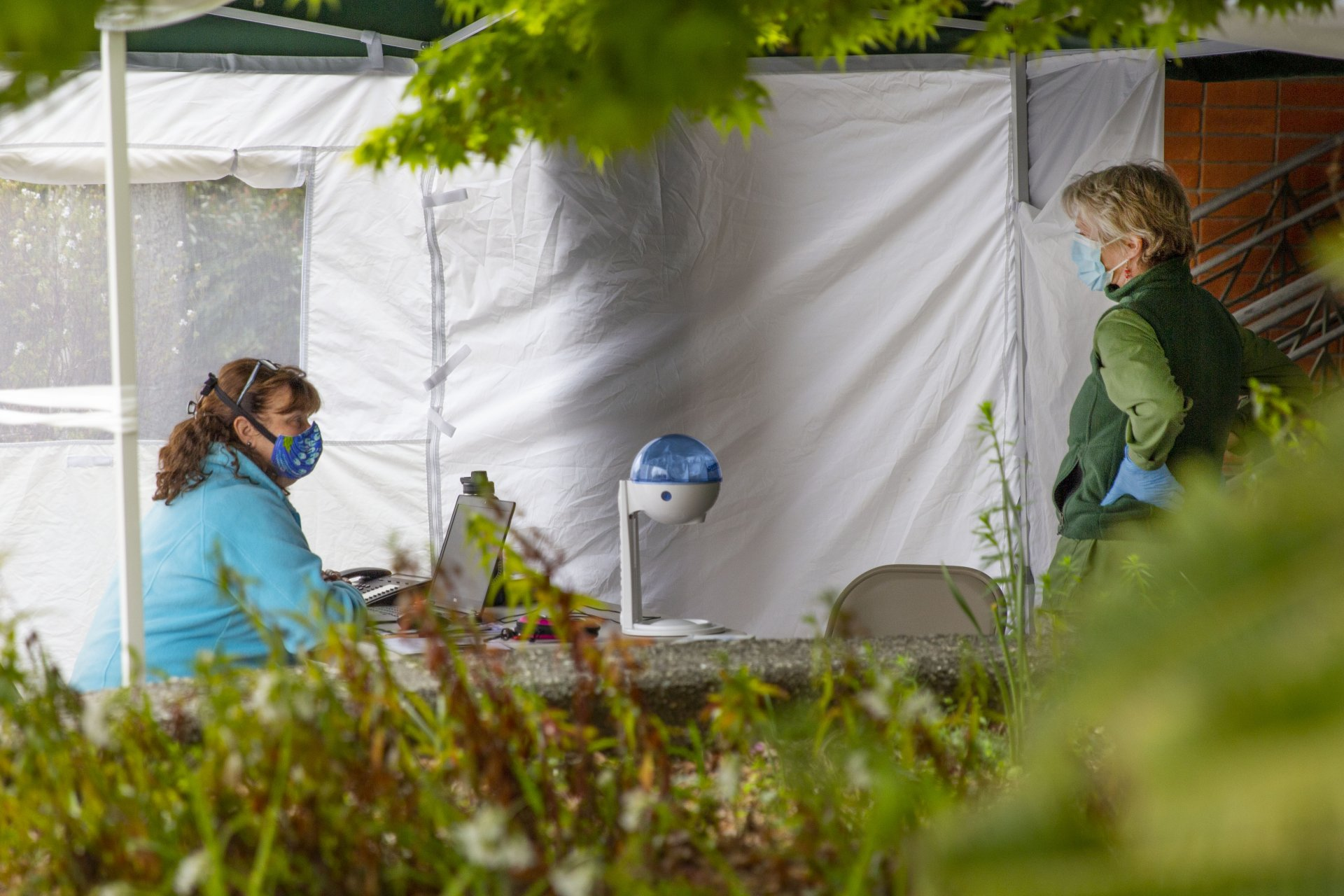 Chris Mis, a registered nurse, and Karin Rodamer, a medical assistant who works at the Student Health Center, talk under a tent outside during the COVID-19 pandemic on April 17. | Photo by Thomas Lal