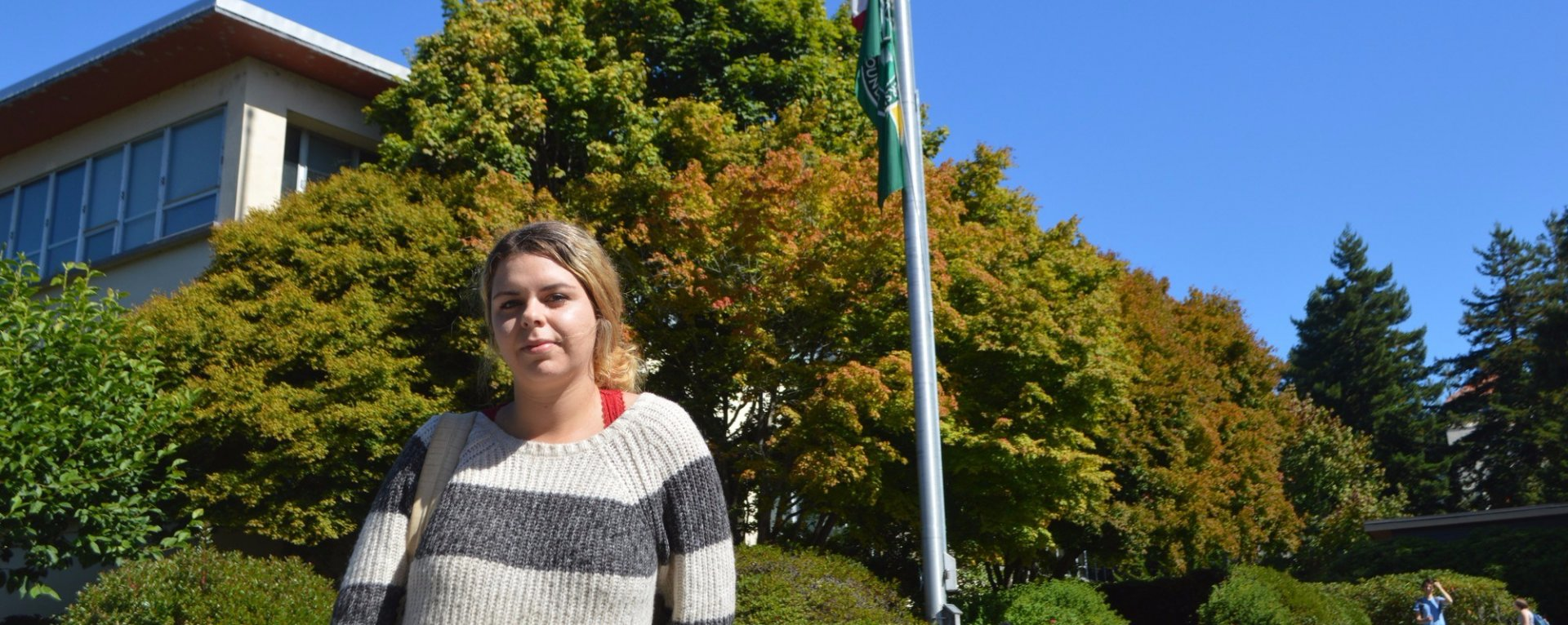 Macy Suchan, 23-year-old senior at HSU stands in front of the half-staff flag on Oct.2 2017. Photo credit: Lora Neshovska