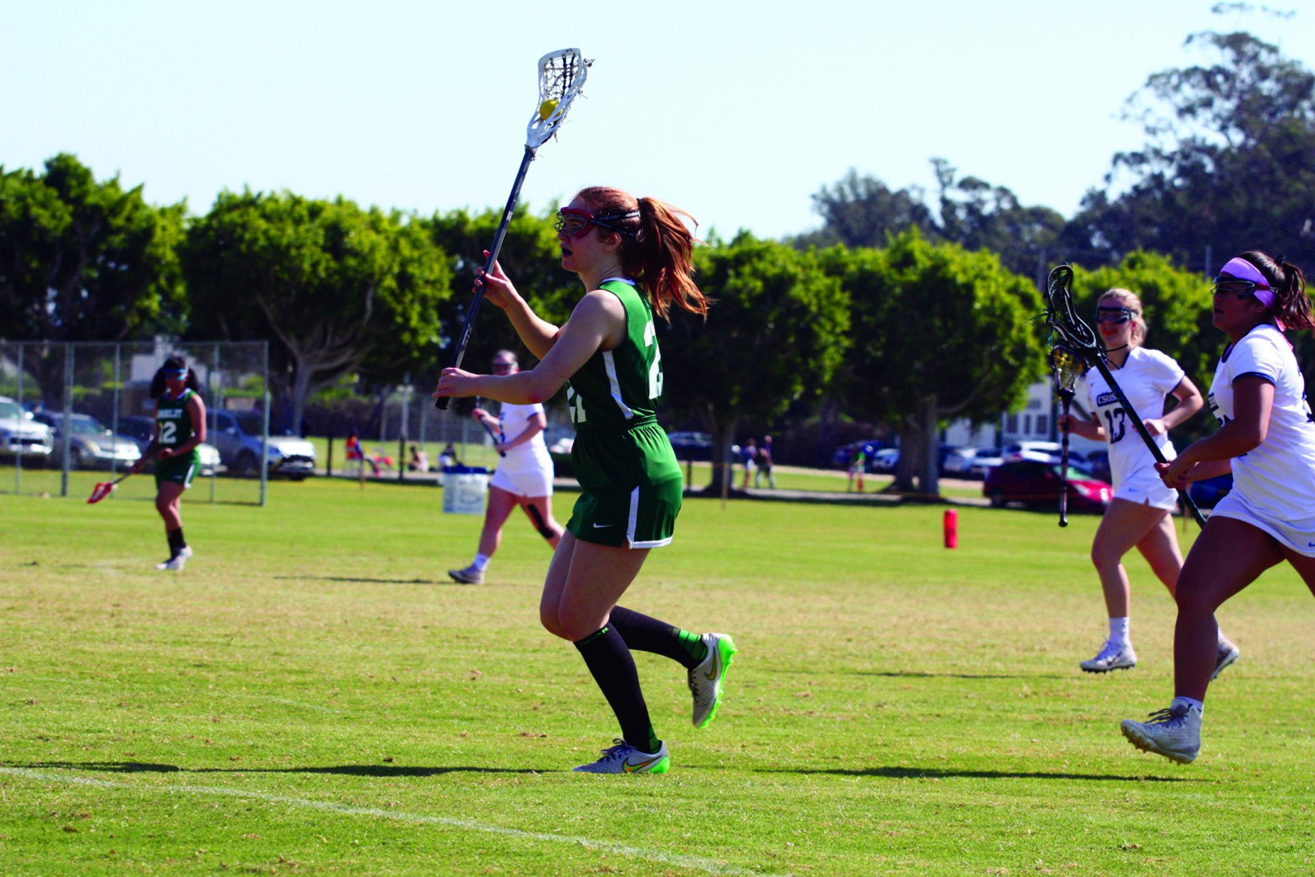 Kiya Guire, #21 for women's lacrosse, gets ready to make a shot. | Photo by Thomas Lal