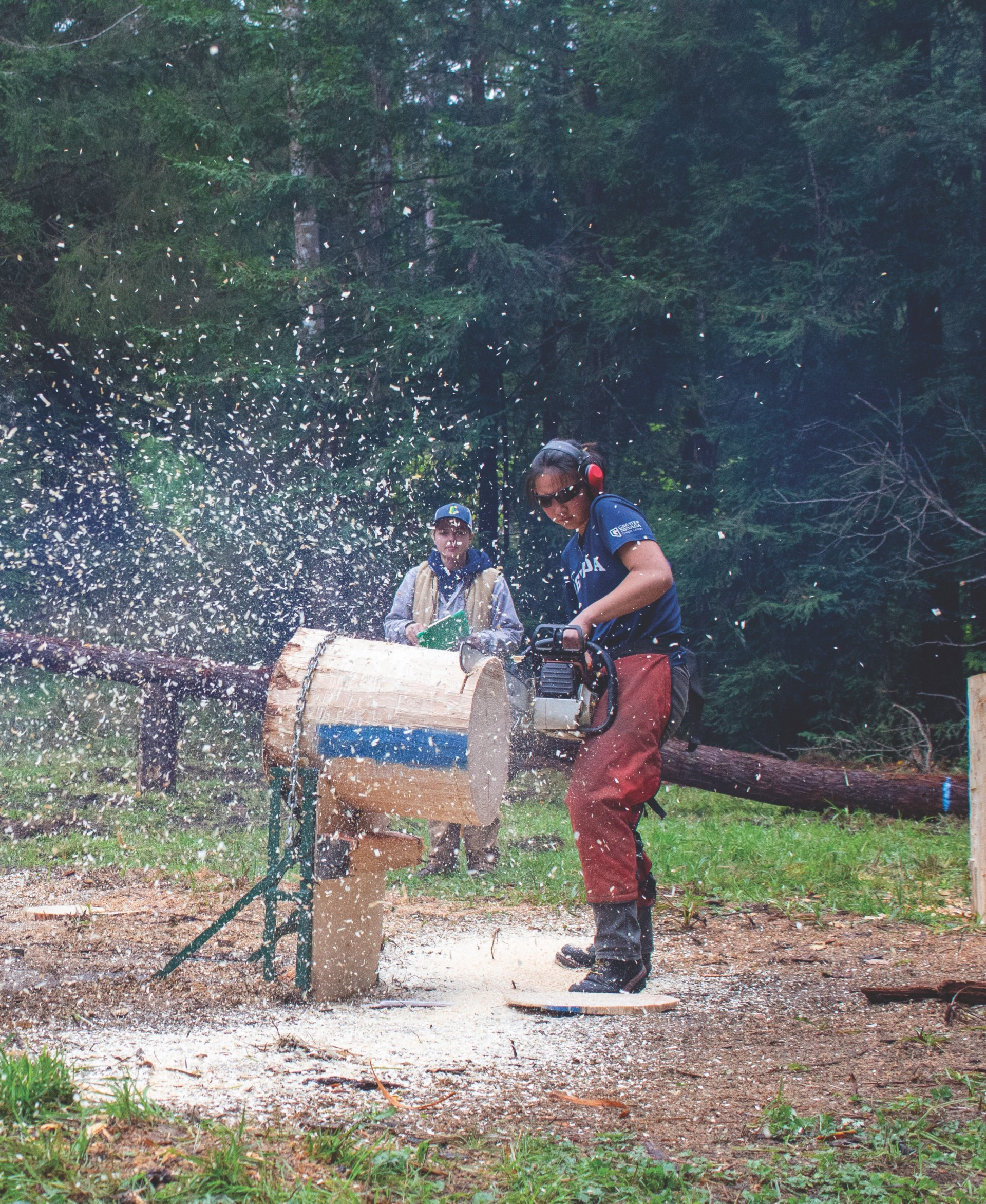 Ginny-Mei Adams of University of Nevada, Reno sending saw dust into the air as her chainsaw digs into a log.   Photo by Alberto Muro.