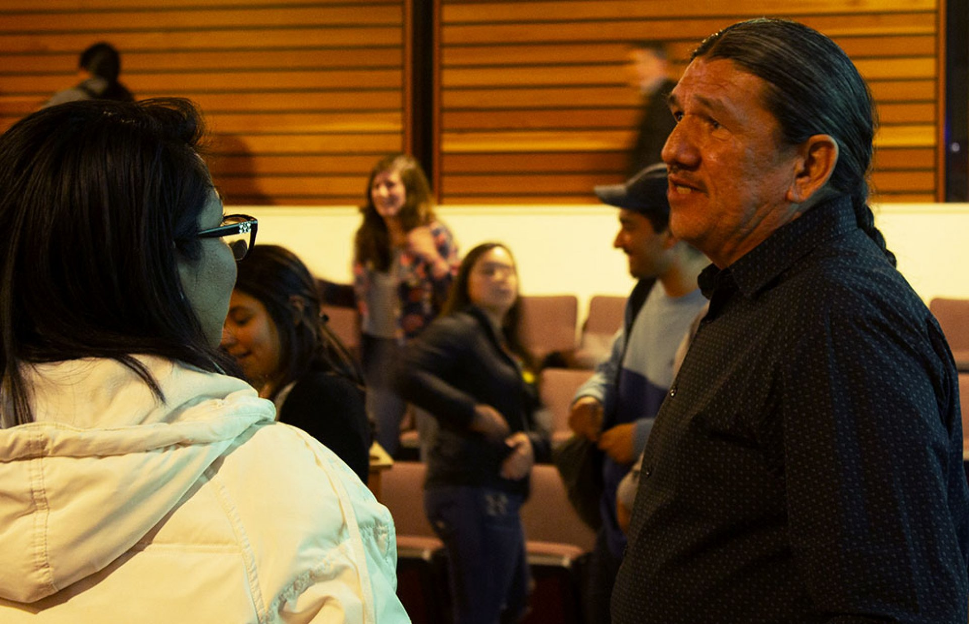 Ron Reed speaking with a student after the panel about concepts that were mentioned that night. March 5.