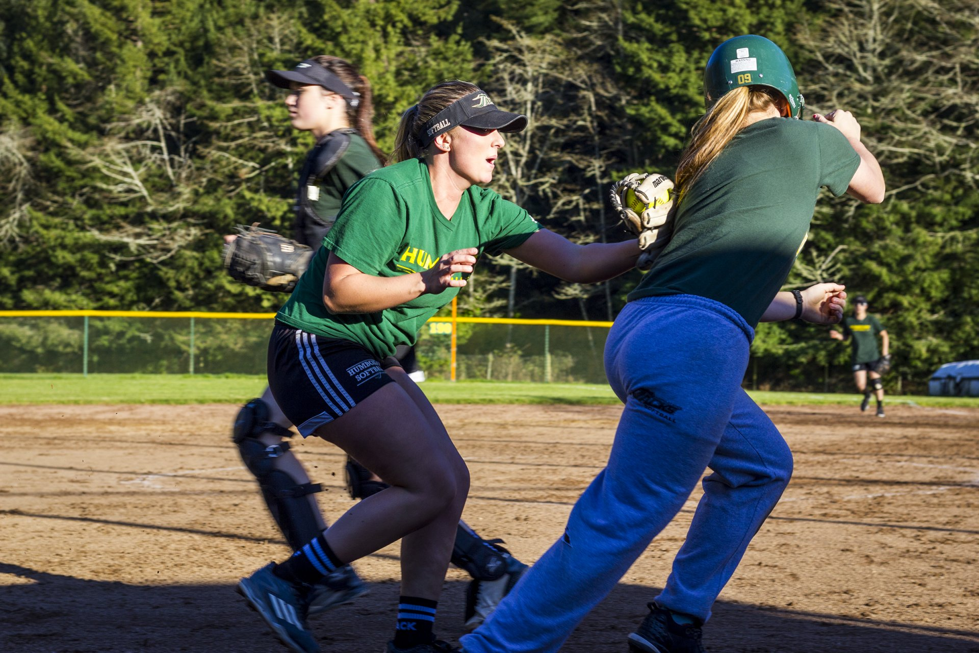 Rachel Barker (center) tags a teammate rounding third base during practice for the Humboldt State University softball team on Feb. 13. Photo by Diego Linares.