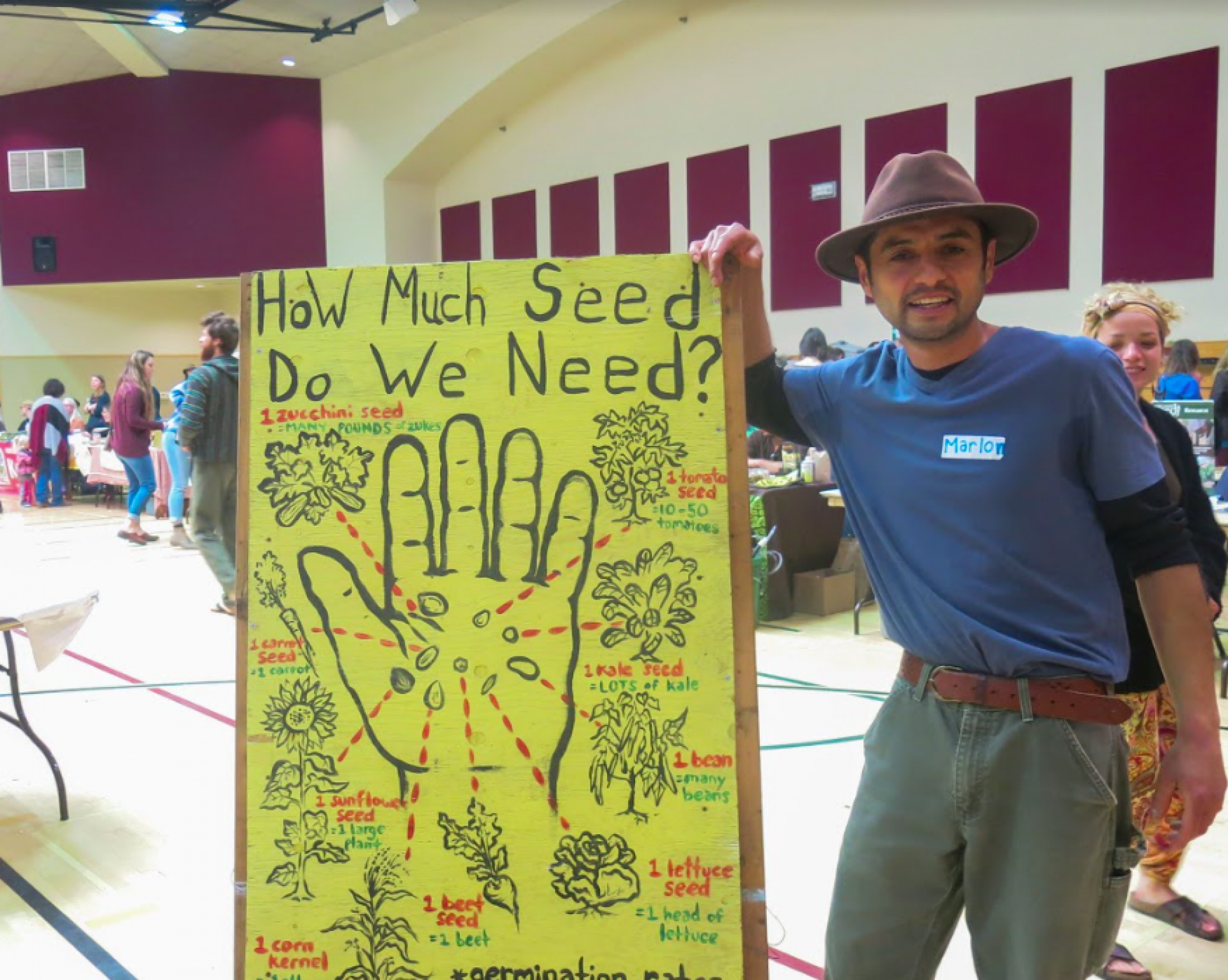 """Marlon Gil, a HSU wildlife graduate and self-proclaimed """"permie,"""" poses at the annual Seed and Plant Exchange hosted by the Humboldt Permaculture Guild. Photo by Emily Owen."""