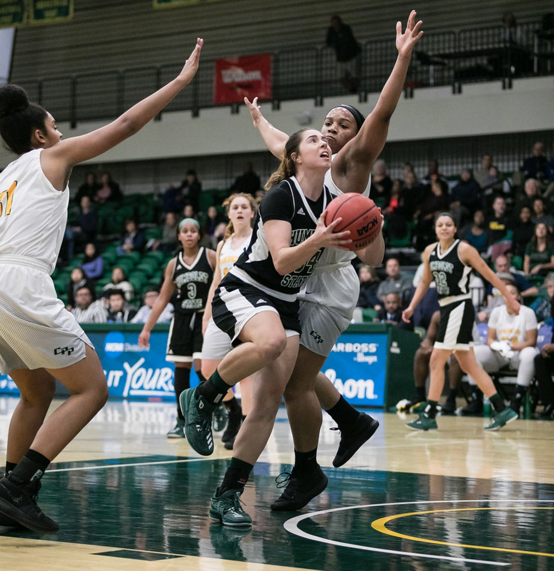 Senior forward Mikaela Shannon goes up for the layup between two Cal Poly Pomona players. The Jacks beat Pomona 69-53 and move on to the CCAA championship.  Photo by Trent Preston (CPP).