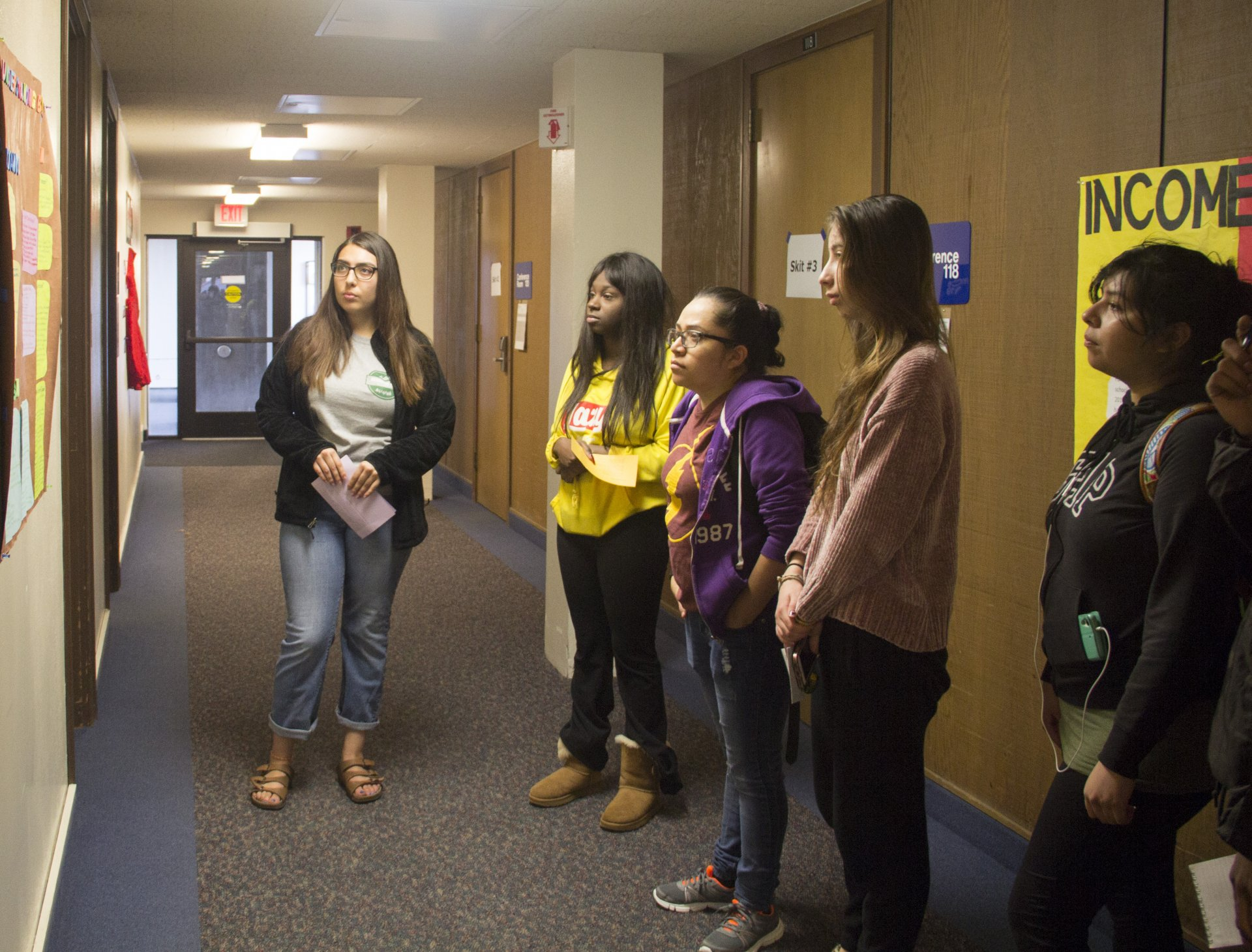Tour guide Samantha Mariscal (left) stops to present a poster as she leads a group to the next skit in the Tunnel Of Oppression on Feb. 15. Photo by Surya Gopalan.