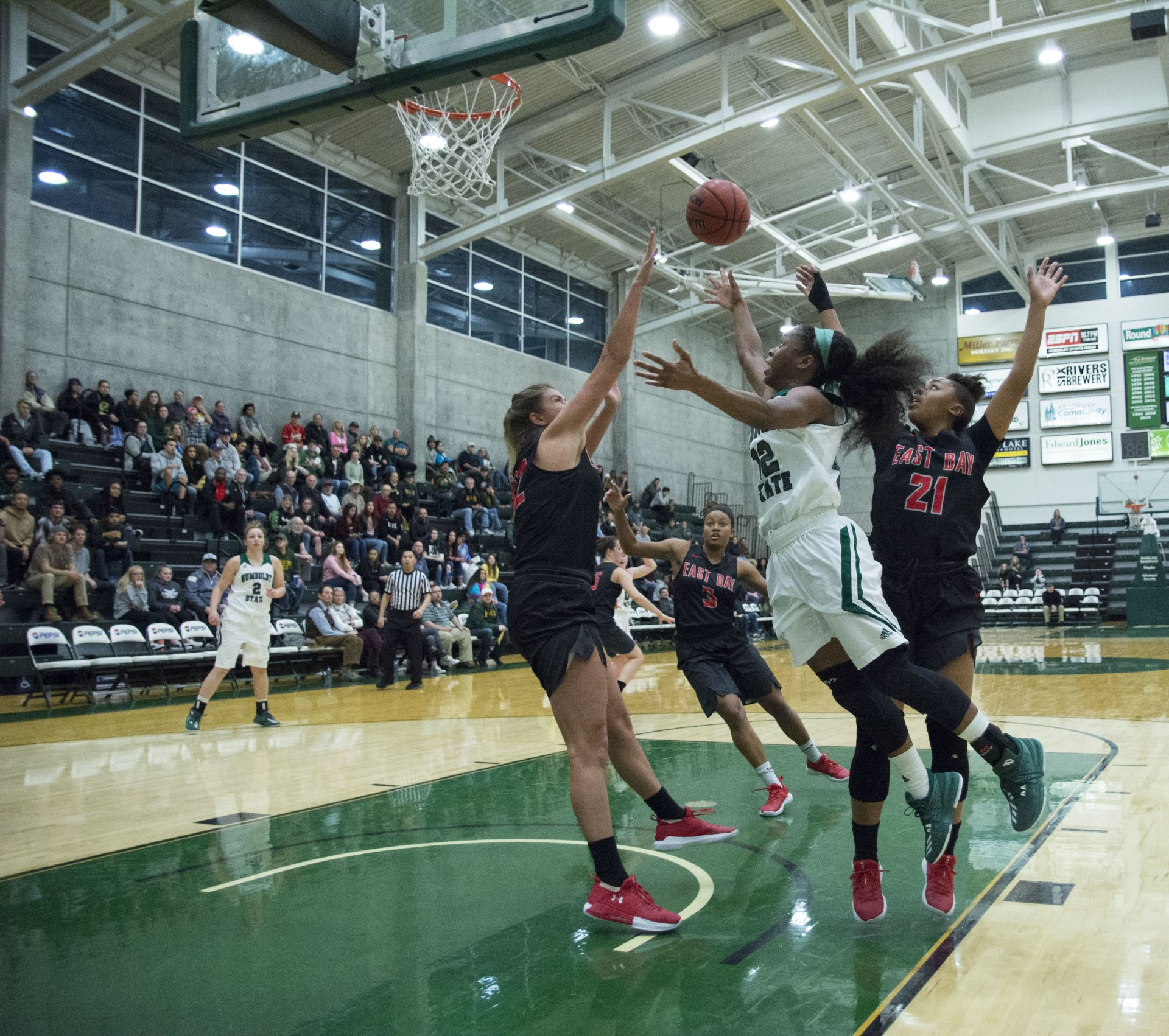 Tyla Turner (#12) floats between Cal State East Bay defenders Kayla Blair (#21) and Savannah McGill (#32) for the layup. | Photo by Zac  Sibek.