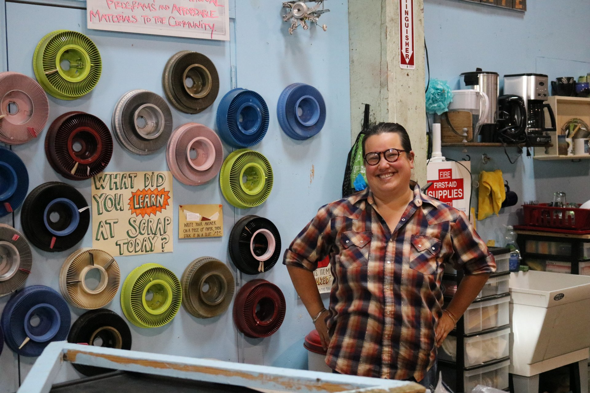 Malia Matsumoto stands surrounded by up-cycled materials in the tutorial area in SCRAP Humboldt in October 2018. | Photo by Chelsea Wood
