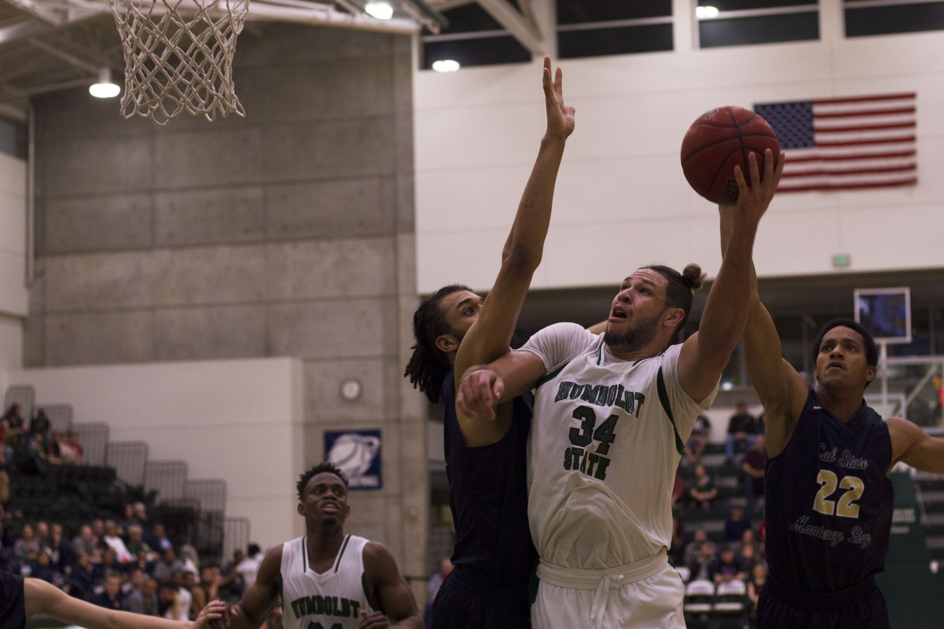Davasyia Hagger evades a California State University, Monterey Bay defender with a spin move and uses his left hand to lay up a shot in the 87-79 Humboldt State University victory in the Lumberjack Arena on Feb. 3. Photo by Diego Linares.