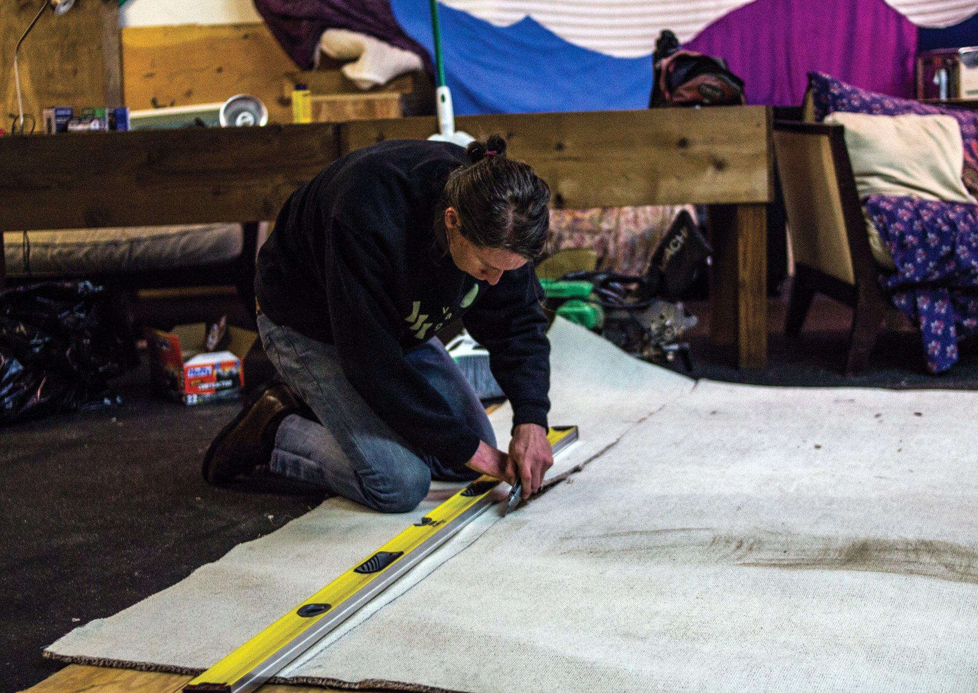 (Photo by Tony Wallin) Humboldt State University alumni Zev Smith-Danford cuts carpet for the stage June 10, 2015 inside Outer Space June 10 an all-ages safe and sober community space. Smith-Danford is a co-creator of the Breakfast All Day (B.A.D.) collective that calls Outer Space home.