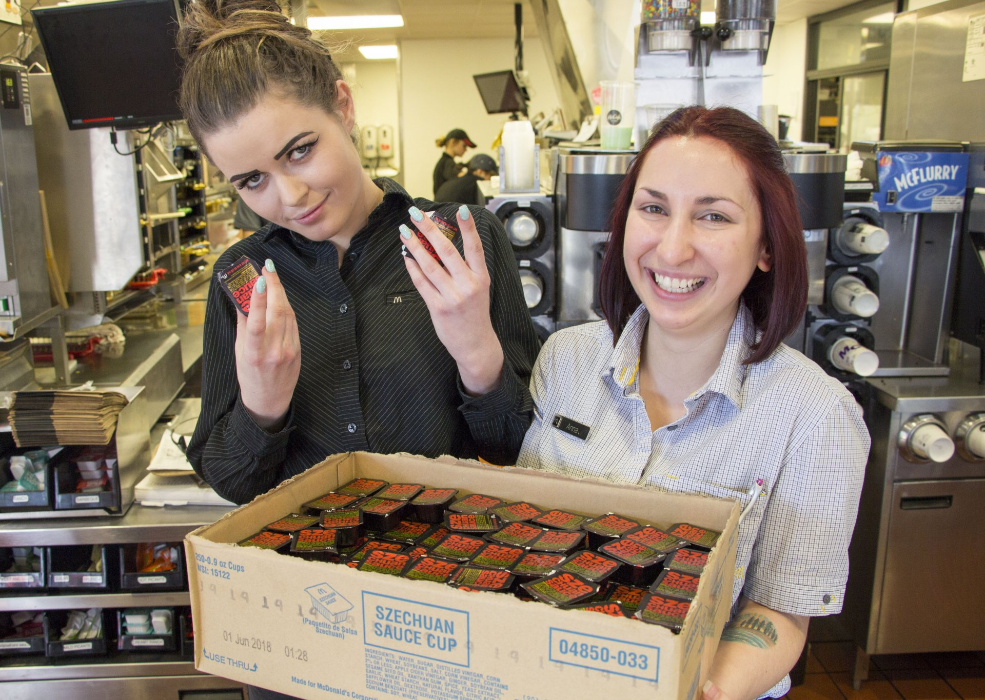 Shift manager Ciana Johnson (left) poses with two cups of Szechuan sauce, as store manager, Anna Lueras, smiles with a box of the sauce on Feb. 24. Photo by Garrett Goodnight.