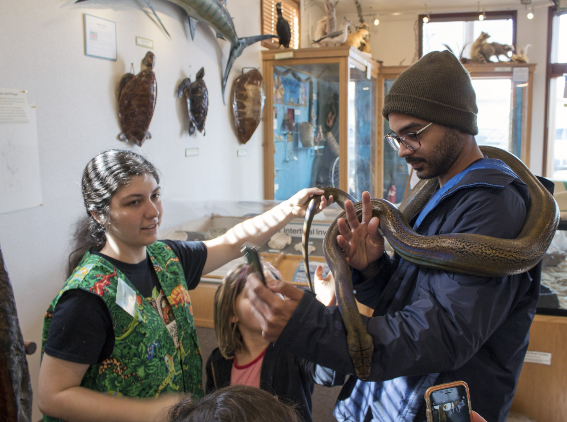 HSU student Taylor Sweet (left) with visitors at the HSU Natural History Museum in Arcata on March 3. Photo by Kyle Orr.