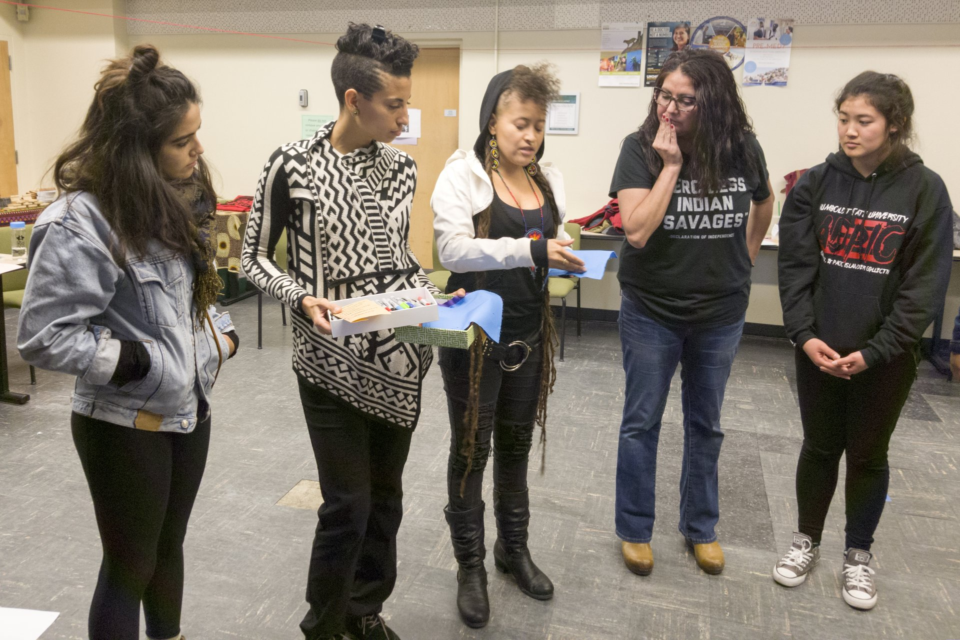 Namia Penniman (second from left) and Alexia Garcia (center) offers workshop attendees fabric to write a message for their S.T.I.T.C.H.E.D. project. Photo by Luis Lopez.