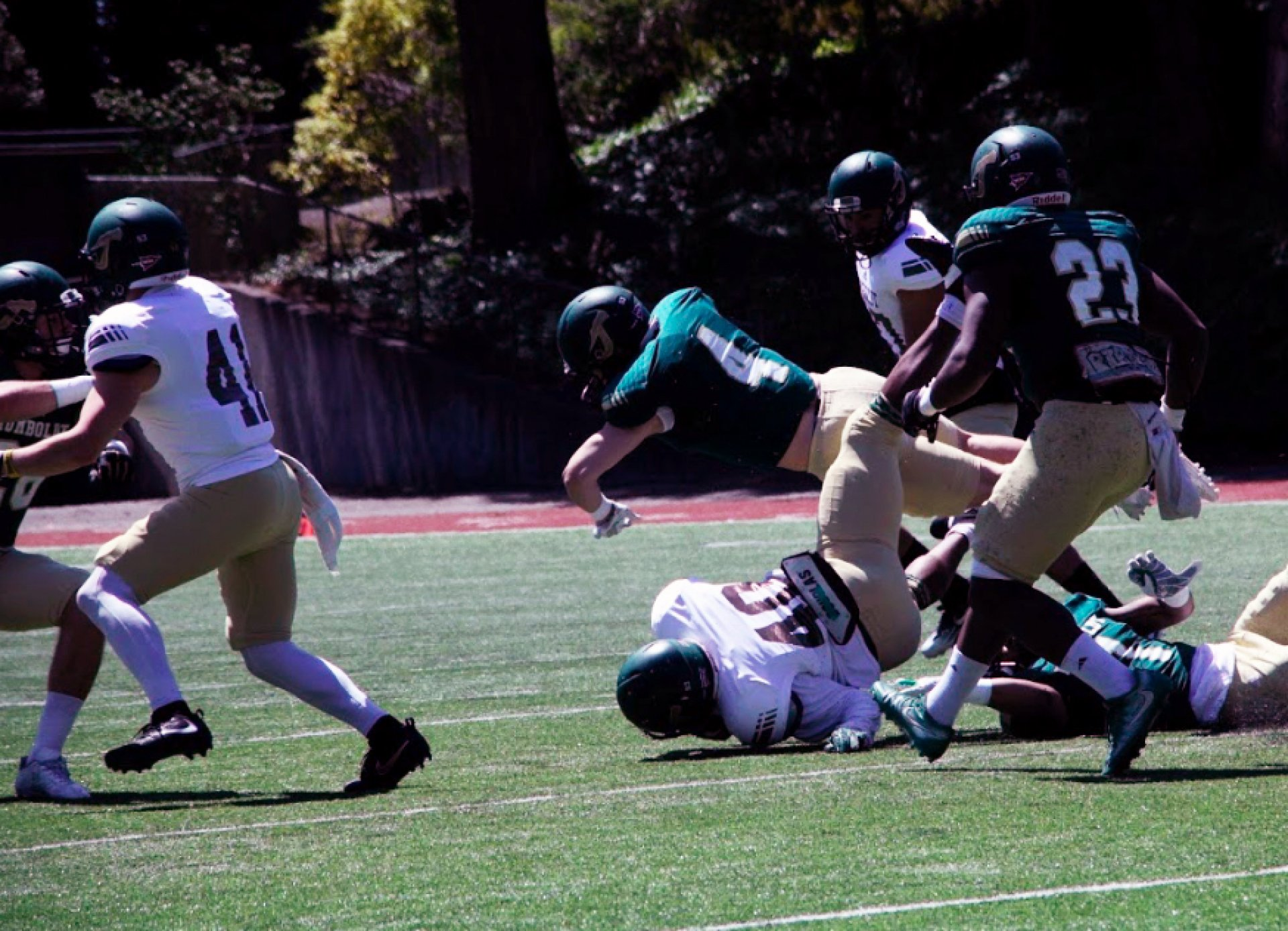 Adam Herrera (#4) and Ju'wan Murphy (#1) tackle the running back during the Spring Football game on April 21 at the Redwood Bowl. Photo by Garrett Goodnight.